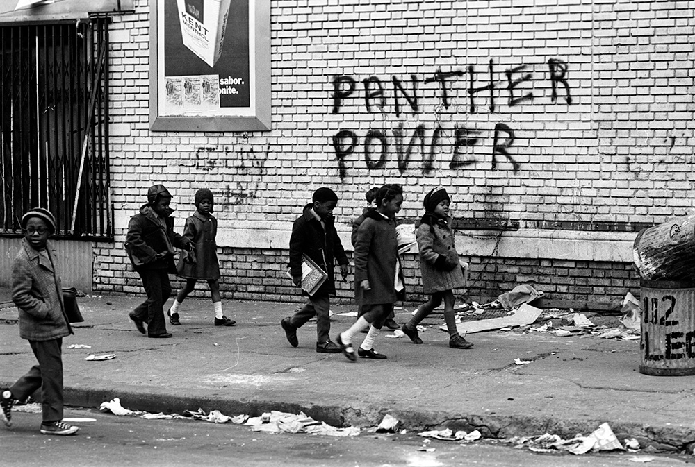 A group of seven small children walk to school with books in hand. From Stanley Nelson's 'The Black Panthers: Vanguard of the Revolution.' Photo courtesy of Stephen Shames.