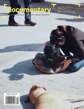 Cover of Spring 2021 issue of Documentary magazine with filmmaker kneeling on the ground, shooting a stray dog, also lying down on its side