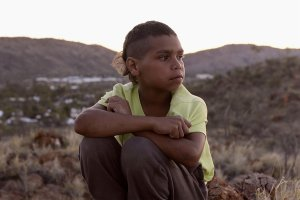 A young Dujuan Hoosan is sitting on a hill, looking pensively to his left. He is from the Arrernte Nation, group of Aboriginal Australian peoples from Central Australia.