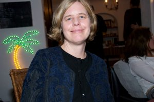 The late Beth Bird sits in a restaurant, smiling; she has short blond hair, and is wearing a blue jacket over a black shirt.