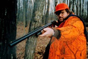 Michael Moore in orange, holding a rifle
