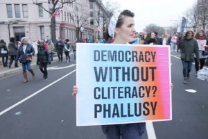 """A woman is particpating in a demonstration on a city street; she carries a sign that reads """"Democracy without cliteracy? Phallusy."""""""