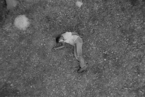 Ambroise Ruzidana as Joe in Ibrahim Shaddad's 'Hunting Party.' He is wearing a t-shirt and trousers, and is lying on the ground. Courtesy of Flaherty Seminar.