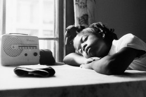 Black-and-white image of a young Black girl listening to the radio with her eyes closed. From Garrett Bradley's 'America.' Courtesy of Museum of Modern Art
