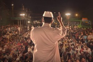 A man with brown skin in a white checkered shirt and white hat standing in front of a crowd. Still from 'An Insignificant Man' by Khushboo Ranka & Vinay Shukla. Courtesy of IFFLA.