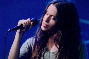 Singer Alanis Morissette, a white woman with long black hair, is performing on stage against a blue lit background; she is holding a microphone, and her eyes are closed, From Alison Kaynman's 'Jagged.' Courtesy of TIFF.