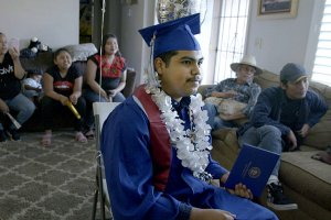 Denilson Garibo is a young man in a blue graduation gown. He is wearing a graduation hat and has a garland of white plastic flowers around his neck. He is surrounded by family members. From Peter Nicks' 'Homeroom.' Courtesy of Hulu