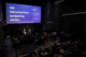"""Two people sit in front of an audience. The projection behind them reads """"ida documentary screening series."""" From a 2019 IDA Screening Series conversation with 'The Amazing Johnathan Documentary' team."""