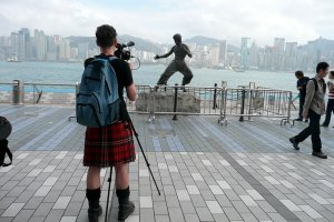 A cameraperson wearing a kilt filming a Bruce Lee statue in Hong Kong. From Mark Cousins' 'The Story of Film: An Odyssey'. Courtesy of Music Box Films.