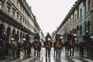 A group of policemen in riot gear and on horseback line up across a city street. From David Dufresne's 'The Monopoly of Violence.' Courtesy of CPH:DOX