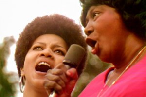 Two Black women singing a duet at the Harlem Cultural Festival. Mavis Staples (left) is wearing hoop earrings and Mahalia Jackson (right) is in a pink shirt. Courtesy of Searchlight Pictures.
