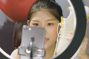 """A young Chinese woman recording herself on an iPhone, holding a sneaker. There is a ring light in front of her. Image from Jessica Kingdon's """"Ascension."""" Courtesy of Tribeca  Festival"""
