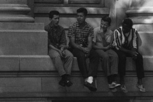A BW photo of four young boys—one Black, three white—sitting on a building ledge