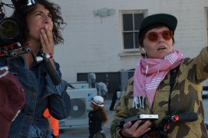 Cinematographer Jenni Morello, the author of this essay, is at left holding her camera in her right arm, her left hand is covering her mouth, and she's looking to her upper left. Director Ana Veselic is at right, holding a sound monitor in her right hand and looking and pointing to her upper left.