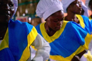 African women chefs in white hats and blue and yellow uniforms.