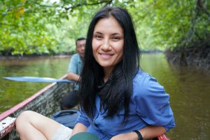 Allison Hanes, a woman with light skin and long black hair, sits in a small boat on a river. An older man with brown skin and dark hair sits behind her. Image courtesy of Hanes.