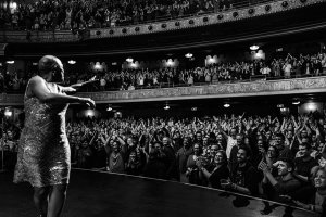 Sharon Jones performing on stage to a cheering crowd