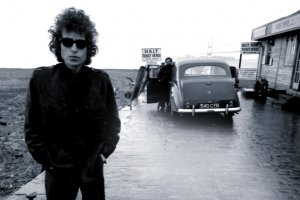 Bob Dylan is standing next to a strip mall