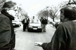two middle-aged men are talking to each other in the middle of the street, facing a group of men surrounding a car