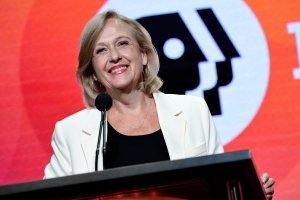 PBS President and CEO Paula Kerger at a podium, wearing a white blazer over a black blouse with the PBS logo behind her.