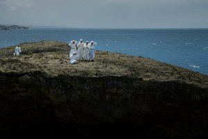Group of people in white robes on a cliff overlooking the ocean