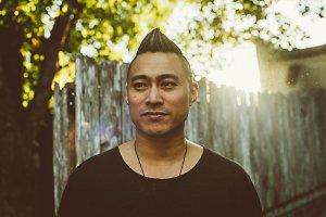 PJ Raval is an Asian man with a short mohawk and high fade, dressed in a round-neck black tee. He is in front of a fence next to a tree.