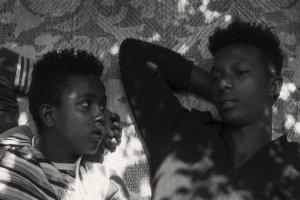 Black and white photo of two young Black men lying on a mat. (l. to r.) Mohammed Arif and Ibrahim Mohammed, two boys from Harar, Ethiopia, as seen in Faya Dayi, directed by Jessica Beshir. Courtesy of Merkhana Films.