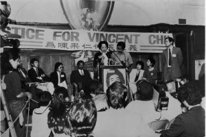 The photo captures a rally for justice for Vincent Chin, who was murdered in 1982 in Detroit in an anti Asian hate crime. At  the podium is Vincent Chin's mother; seated behind her are several activists from the Asian American community, as well as civil rights leader Jesse Jackson.