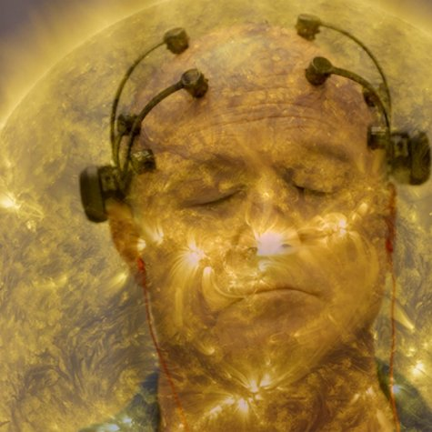 A man, who is particiapting in a neuroscience focus group, has his eyes closed, and is wearing a device on his head comprised of four neurosensors attached to the top of his head and twolarger sensors above each ear. He in enveloped in a golden aura that resembles the sun.