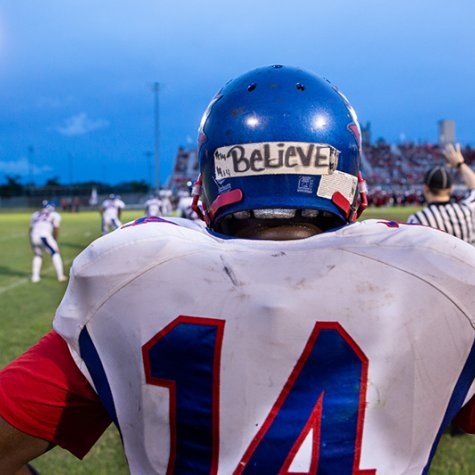 Back of a football player facing the field, his blue helmet has a horizontal tape with BELIEVE written with sharpie.