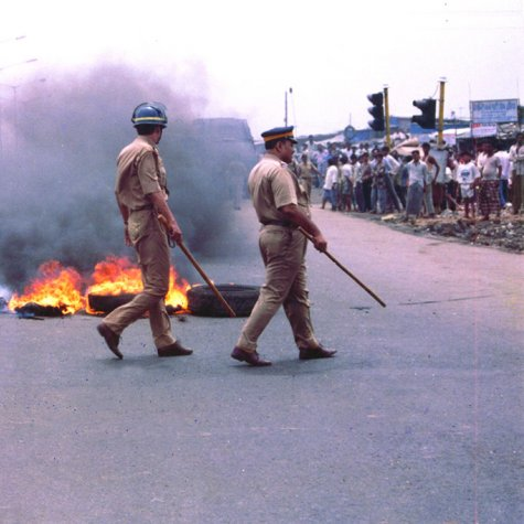 Tires burning in the middle of the road, two Indian police officers are walking by with batons in hand and crowd watching on the side of the road