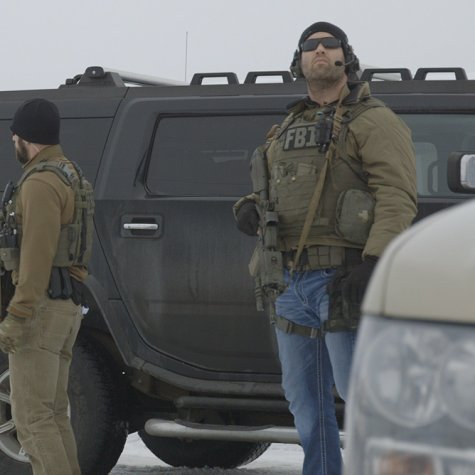 Two FBI agents in gear standing next to a big black armored SUV
