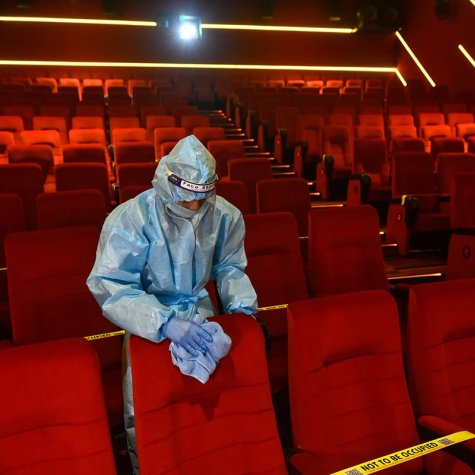 Person in a hazmat suit cleaning a seat inside of an empty movie theater.