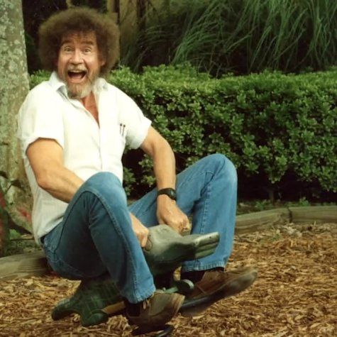 Bob Ross is white artist with a brown afro and a mostly grey beard. He is riding a bouncy alligator ride in a playground. He is wearing a white shirt and blue jeans. Image from Joshua Rofé's 'Bob Ross: Happy Accidents, Betrayal & Greed.' Courtesy of Netflix.