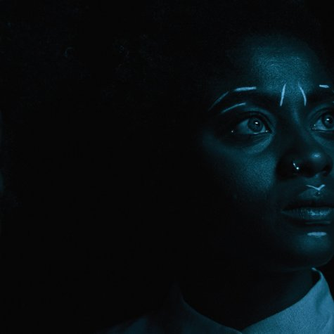 Two young Afro-German women photographed in low light. They have white traditional markings drawn on their faces. Image from Anna Zhukovets' and Kokutekeleza Musebeni's 'Door of Return'. Courtesy of BlackStar Film Festival.