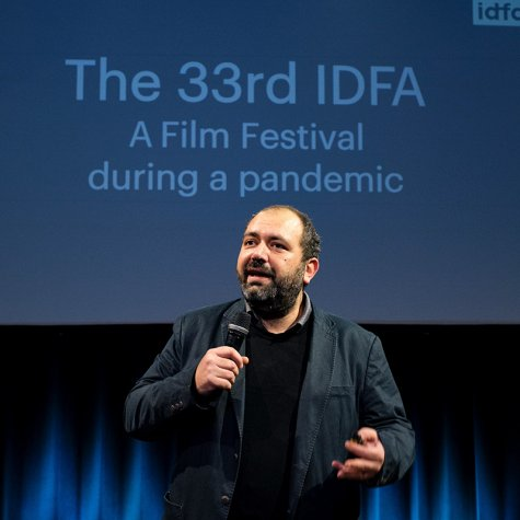 IDFA Artistic Director and filmmaker Orwa Nyrabia is a Syrian man with a beard and short hair. He is wearing a black jacket and a sweater while addressing the in-person and virtual audience at IDFA 2020. There is a screen behind him. Photo: Coen Dijkstra. Courtesy of IDFA