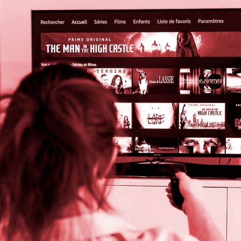 A woman holding a TV remote control facing a screen displaying the homepage of Prime Video.