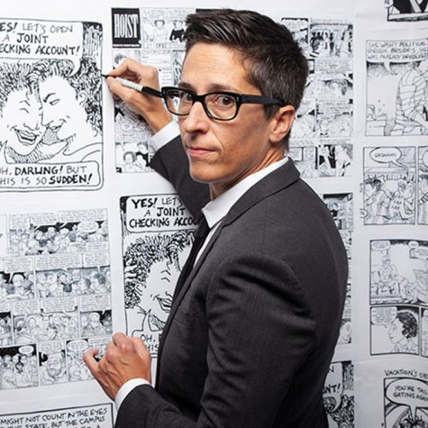 Alison Bechdel is a white woman with short hair black-rimmed glasses. She is wearing a black suit and is holding a marker to a wall of her comics. Image from Vivian Kleinman's 'No Straight Lines: The Rise of Queer Comics'. Courtesy of Outfest.