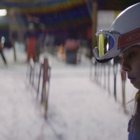 Sarah Rose Huckman, a young transgender woman in skiing gear. Ski resort behind her. She is the protagonist of 'Changing the Game' (Directed by Michael Barnett)