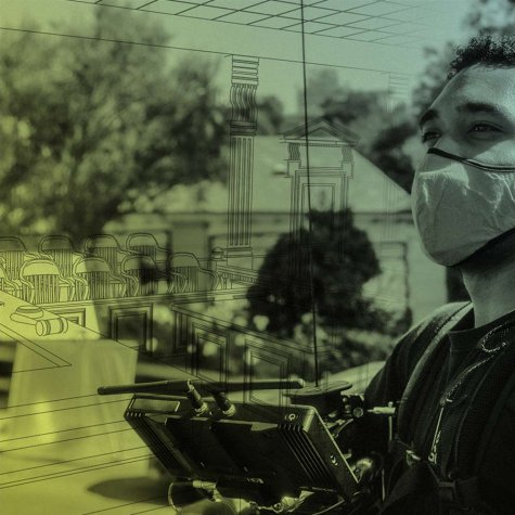 an adult wearing a mask, working a camera monitor