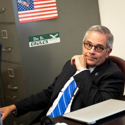 Philly DA Larry Krasner, wearing glasses, a dark suit and a blue-striped tie, sits at an office desk in front of a file cabinet.