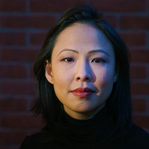 An Asian woman of Malaysian Chinese origin with shoulder-length black hair. She is wearing a black turtleneck & in front of a brick wall.