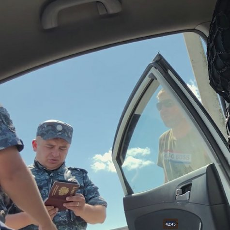 Scene from Welcome to Chechnya where security guard is checking the backup team's passports outside of their car.