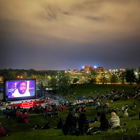 An outdoor nighttime screening: the audience sits on a grassy hill