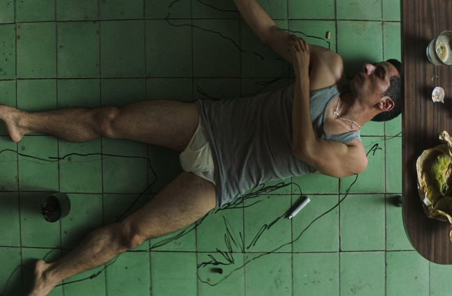 A man with brown skin and short hair, wearing a tank top and underwear, traces himself on the floor.