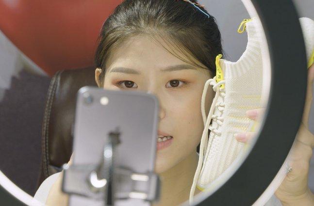 An asian woman with black hair holds up a white tennis shoe in front of a camera and ring light.