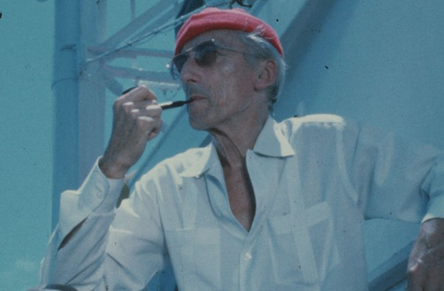 An older white man wearing a red cap, white shirt and sunglasses. He is smoking a pipe.