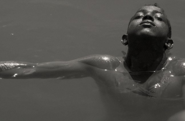 A black and white picture of a boy with Black skin swimming in water.