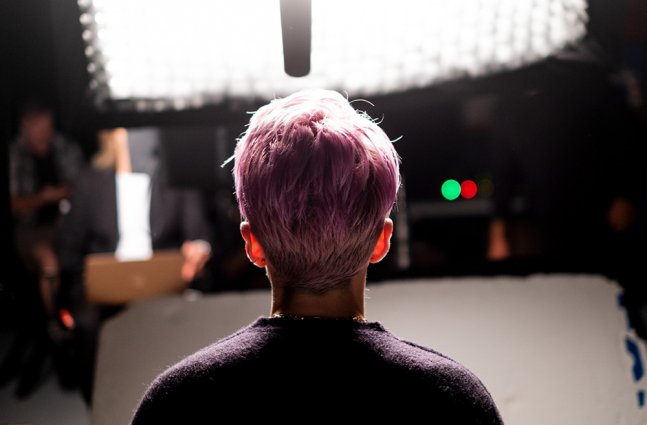 The back of a woman with pink hair's head.