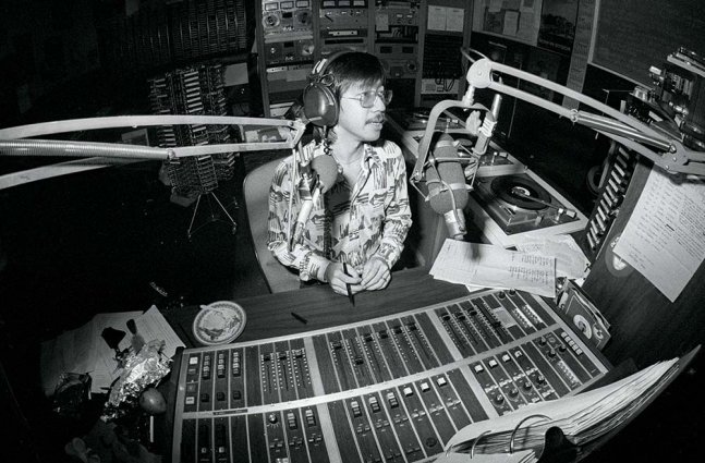 A black and white photo of an asian man in a patterned button up. He sits in a recording studio.